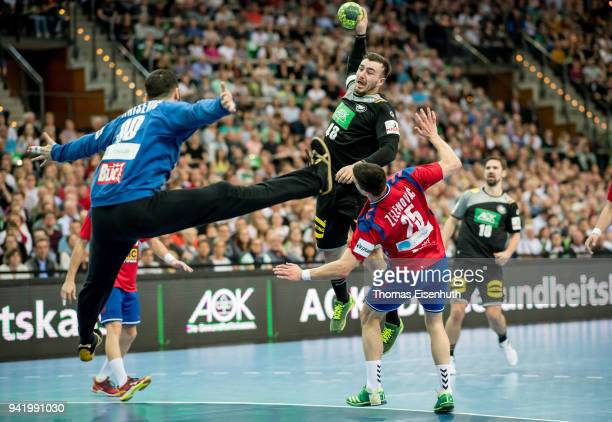 Jannik Kohlbacher of Germany is challenged by Nemanja Zelenovic and Tibor Ivanisevic of Serbia during the handball international friendly match...