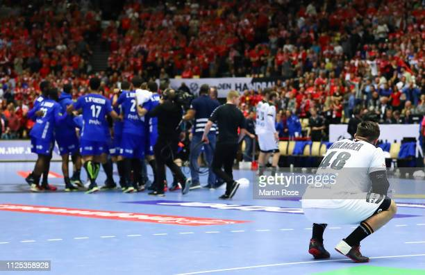 Jannik Kohlbacher of Germany looks dejected as the players and officials of France celebrate winning at the end during the 26th IHF Men's World...