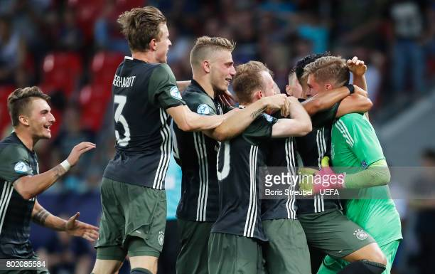 Jannik Pollersbeck of Germany celebrates with his team mates after he saved a penalty from Nathan Redmond of England to win his side the penalty...