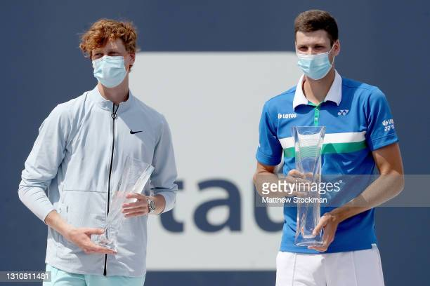 Jannik Sinner of Italy and Hubert Hurkacz of Poland pose at the trophy ceremony during the final of the Miami Open at Hard Rock Stadium on April 04,...