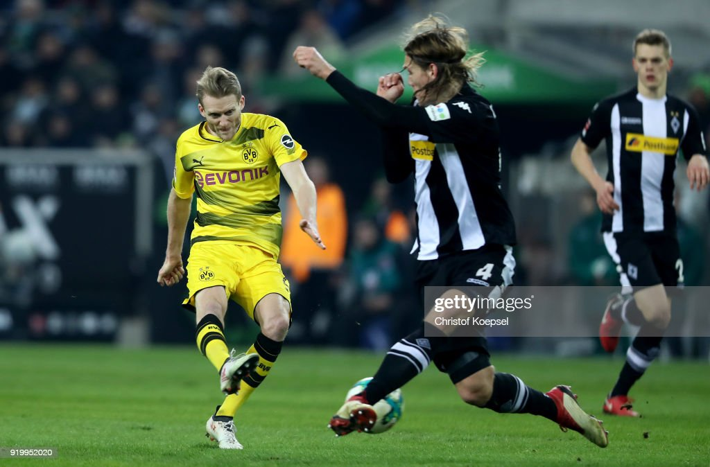 Jannik Vestergaard of Moenchengladbach (R) blocks a shot of Andre Schuerrle of Dortmund (L) during the Bundesliga match between Borussia Moenchengladbach and Borussia Dortmund at Borussia-Park on February 18, 2018 in Moenchengladbach, Germany.