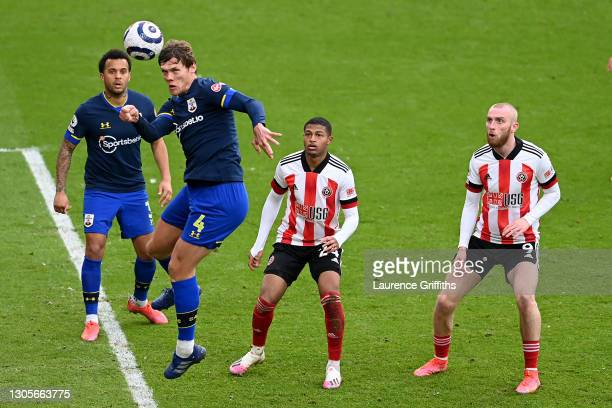 Jannik Vestergaard of Southampton heads clear as Rhian Brewster and Oliver McBurnie of Sheffield United look on during the Premier League match...