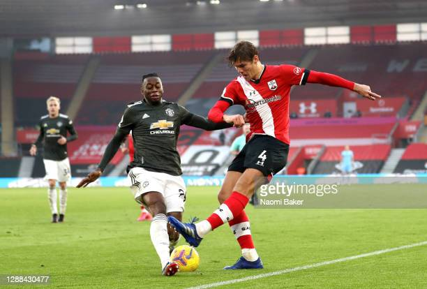 Jannik Vestergaard of Southampton shoots under pressure from Aaron Wan-Bissaka of Manchester United during the Premier League match between...