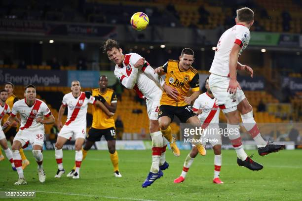 Jannik Vestergaard of Southampton wins a header over Daniel Podence of Wolverhampton Wanderers during the Premier League match between Wolverhampton...