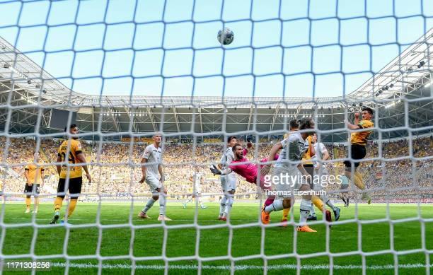 Jannis Nikolaou of Dresden scores his team's first goal past goalkeeper Robin Himmelmann of St. Pauli during the Second Bundesliga match between SG...