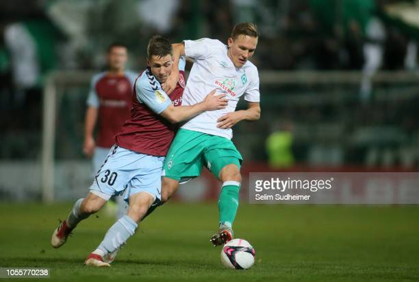Jannis Plaeschke of Flensburg fights for the ball with Ludwig Augustinsson of Bremen during the DFB Cup match between SC Weiche Flensburg 08 v SV...