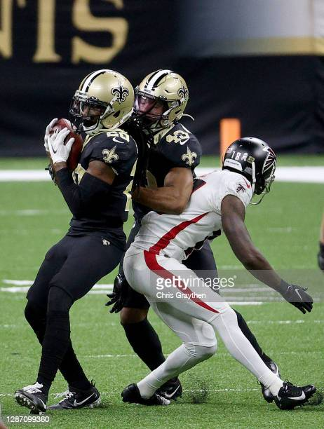 Janoris Jenkins of the New Orleans Saints intercepts a pass intended for Calvin Ridley of the Atlanta Falcons as Marcus Williams of the New Orleans...