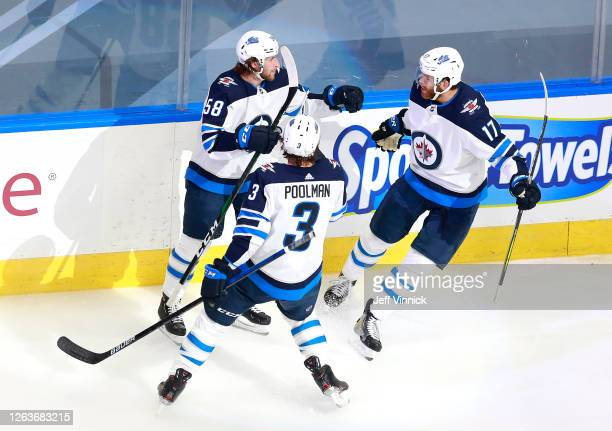 Jansen Harkins of the Winnipeg Jets celebrates his first NHL playoff goal with teammates Tucker Poolman and Adam Lowry in the first period against...