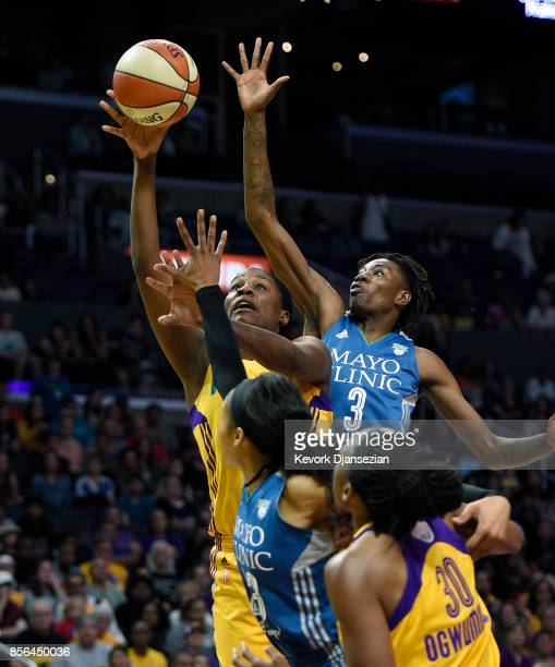 Jantel Lavender of the Los Angeles Sparks shoots under pressure from forward Natasha Howard and Maya Moore of the Minnesota Lynx during the second...