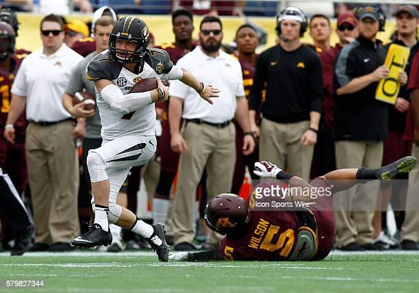 Missouri Tigers quarterback Maty Mauk slips thru the hands of Minnesota Golden Gophers linebacker Damien Wilson in the first half of play at the...