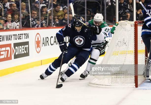 Winnipeg Jets defenseman Jacob Trouba fights off the check of Dallas Stars forward Devin Shore during the regular season game between the Winnipeg...