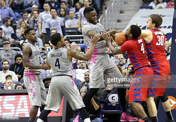 Georgetown Hoyas center Jessie Govan tangles with DePaul Blue Demons forward Myke Henry and forward Peter Ryckbosch over a loose ball during a men's...