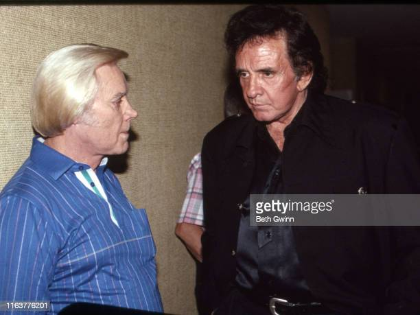 Country Music Singer Songwriter George Jones Johnny Cash talk back stage at Opry House on January 1 1991 in Nashville Tennessee