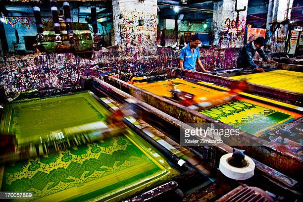 Fabric printing is in progress on automatic fabric printing machines on January 10 2012 in a fabric dyeing factory in Rajasthan India Workers attend...