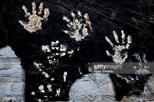 Workers have their hands prints made on a black piece of fabric on January 10 2012 in a dyeing factory in Rajasthan India A piece of black cloth an...