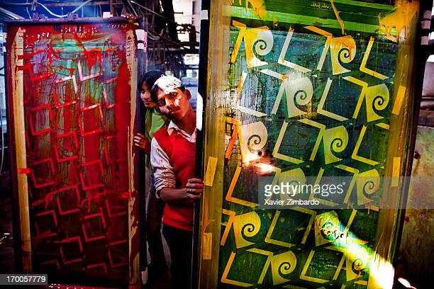Workers hold printing frames loaded with colours to print fabric on January 10 2012 at a fabric dyeing factory in Rajasthan India The fabric is...