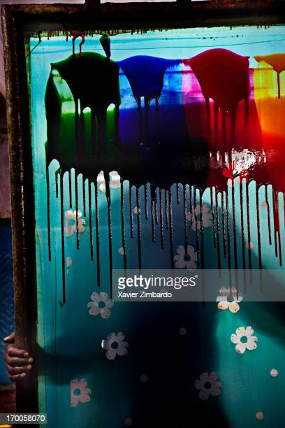 A worker holds up a fabric printing screen botched by accidental spilling of colour dye on January 13 2012 in a dyeing factory in Rajasthan India A...