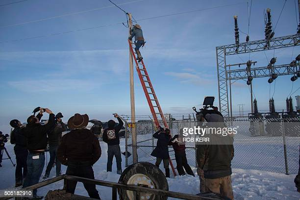 January 15 2016 in Burns Oregon LaVoy Finicum climbs a ladder to disable a power pole remote camera location near the occupied Malheur National...