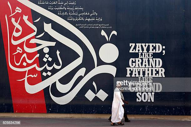January 17 2012 Pedestrians passing a wall mural written in Arabic calligraphy with the words of wisdom of Sheikh Zayed bin Sultan Al Nahyan the...