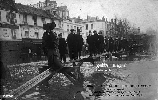 Pedestrians traverse a foot bridge erected during flooding of the Seine
