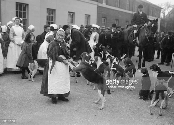 Members and staff from a workhouse greet the dogs from the Chertsey Hunt