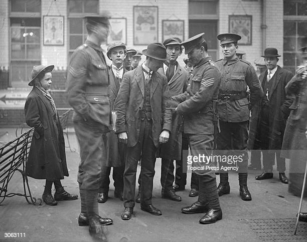 A group of men who enlisted in the British army as part of Lord Derby's campaign undergo an inspection by officers at Mansion House