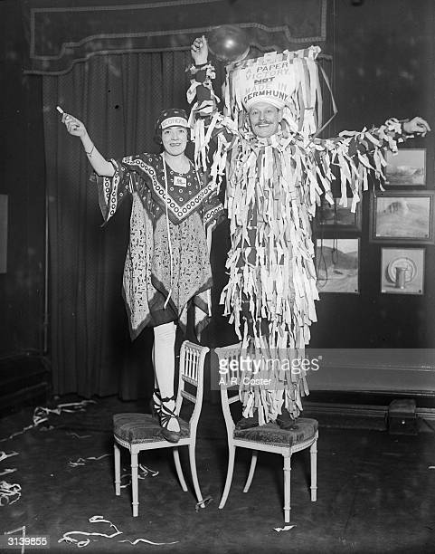 American night at Princes A woman dressed as Economy in a dress made out of scarves and a man in shredded paper and a headdress on which is written...