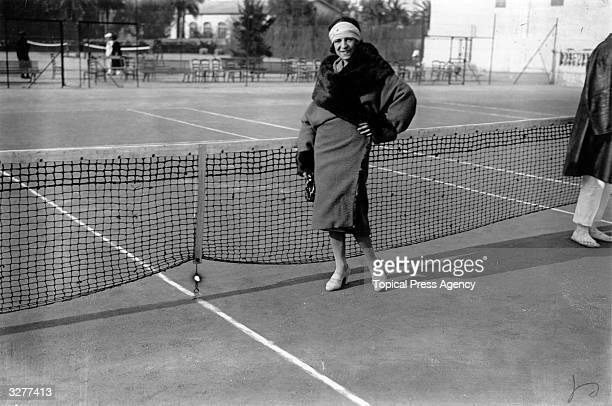 French tennis player Suzanne Lenglen in a fashionable coat at the net on a tennis court.