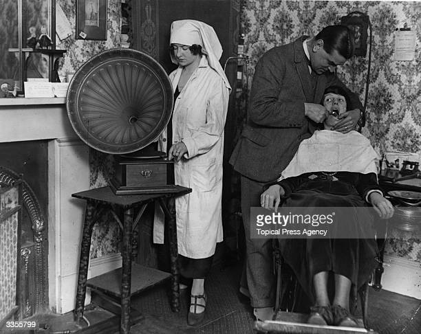 A dental assistant plays loud music on the gramophone to distract a patient from the pain of having her tooth pulled by the dentist