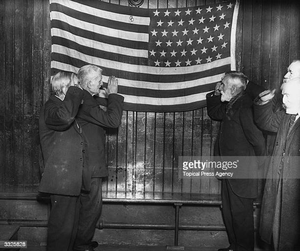 Four American Civil War veterans saluting 'Old Glory' the star spangled banner at their annual dinner at the London Tabernacle Newington Butts London
