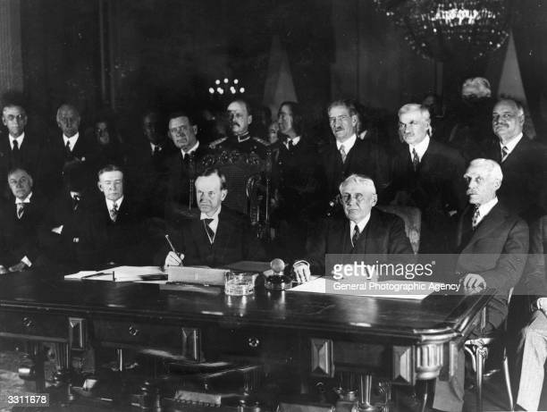 President Calvin Coolidge signing the Kellogg Treaty renouncing war in a session staged for the news reel cameras in the White House Vice President...
