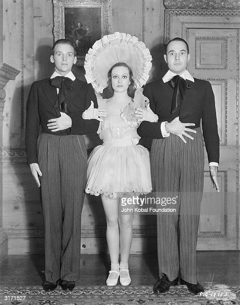 American film actress Joan Crawford attends a New Year's Eve party with her husband Douglas Fairbanks Junior and William Haines .
