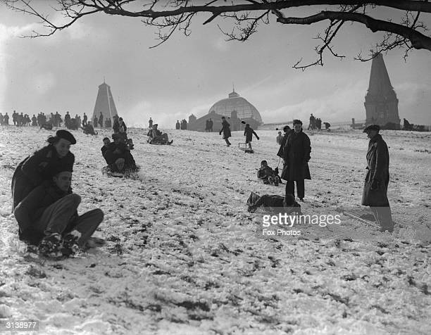People enjoying the snow on slopes by Alexandra Palace in north London