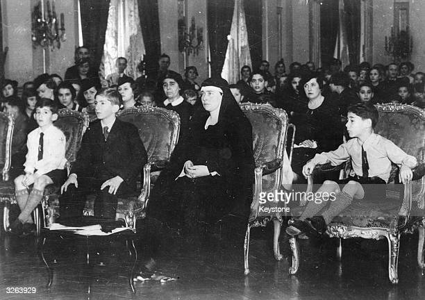 King Peter II King of Yugoslavia from 1934 1945 after the assassination of his father Alexander I He is seated with his mother Queen Marie after the...