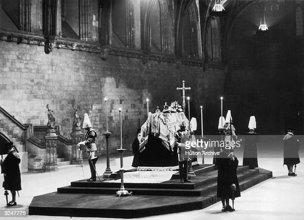The late King George V lying in state in London's Westminster Hall, surrounded by horse guards.