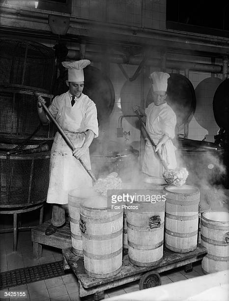 A pair of chefs mixing stew in containers