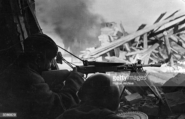 Soviet machinegunners fire at Nazis who had barricaded themselves into houses during street fighting on the outskirts of Stalingrad.