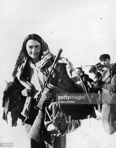 A woman school teacher who became an antifascist partisan of the 'White Patrol' in the mountainous border regions with her husband brandishes a Suomi...