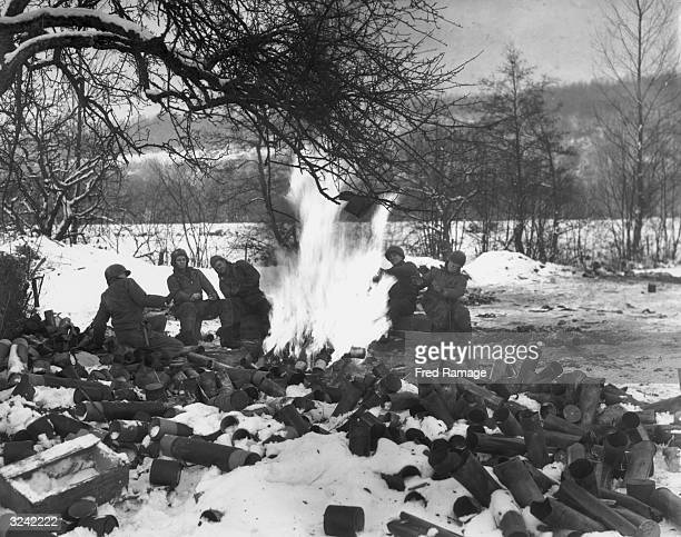 The crew of a 105 gun using a powder charge to start their cardboard cartridge case fire in the Ardennes forest
