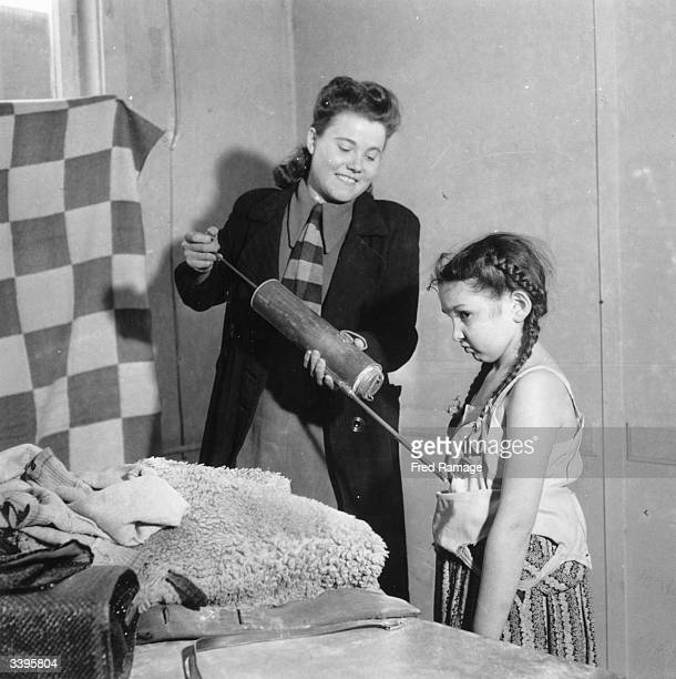 A little Jewish girl from Poland having herself and her clothes disinfected with a large syringe on her arrival at the US camp in the American sector...