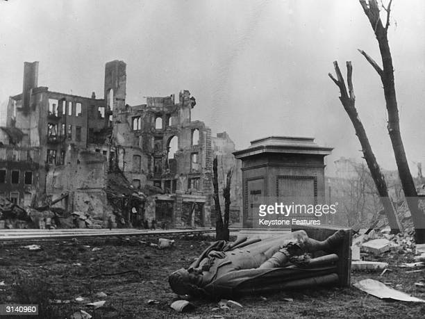 A statue of the German poet Johann Schiller lies on the ground beside its pedestal in war torn Munich just after the end of WW II