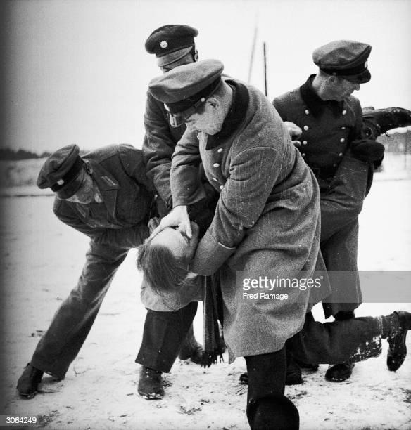 Policemen from the German Police Sports School in Spandau, Berlin restrain a black marketeer who resisted arrest. The school trains members of the...