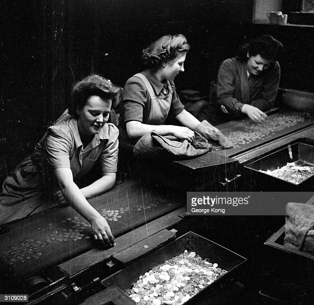 Workers pick out and reject flawed coins from a conveyor belt at the Royal Mint in London Around one per cent of coins are rejected at this stage