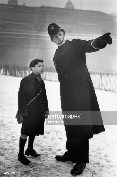Michael Hardy, the son of Picture Post photographer Bert Hardy, asking a policeman the way to Buckingham Palace, London. Original Publication:...