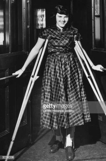 A girl with leg braces smiles while standing with crutches in a doorway