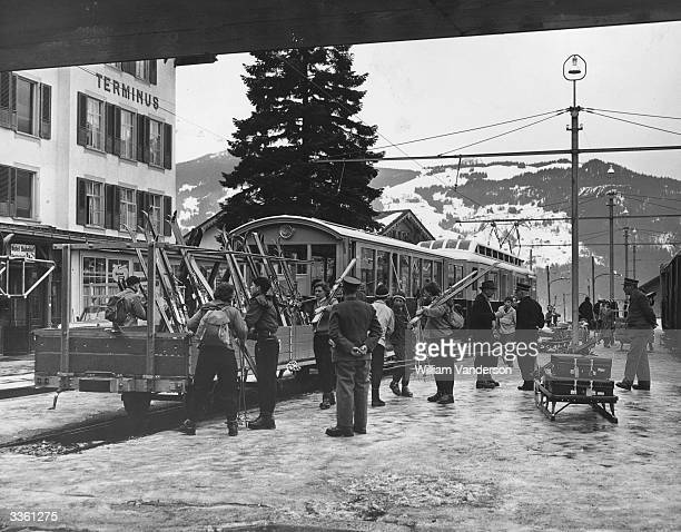 Skiers place their skis in a van attached to the rear of the train at Wengen Switzerland