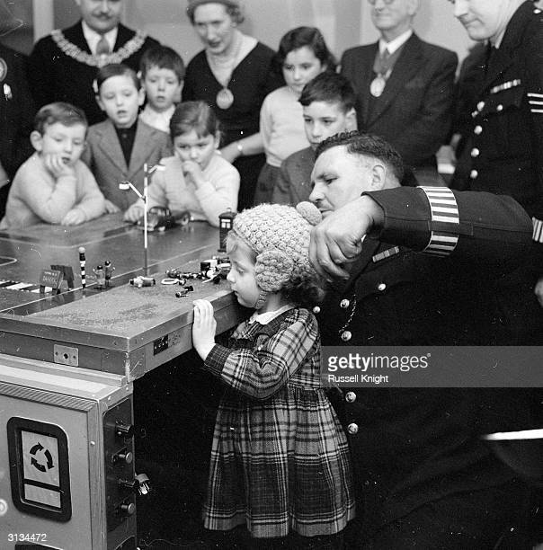 Members of the Holborn Toddlers' Club learn road safety on a tiny model of a pedestrian crossing operated with magnets by PC Stanley Jackman