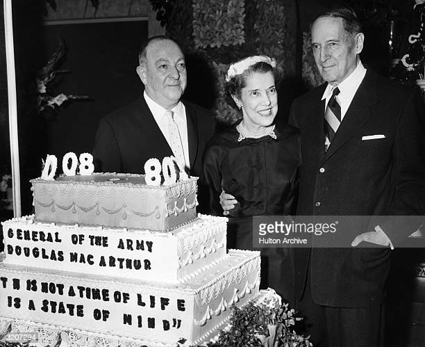 Retired US Army General Douglas MacArthur his wife Jean and Chock Full O' Nuts coffee president William Black pose behind a cake honoring the...