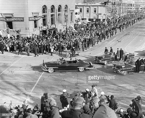 President John F Kennedy is driven through the crowded streets with his wife Jackie on the day of his inauguration.