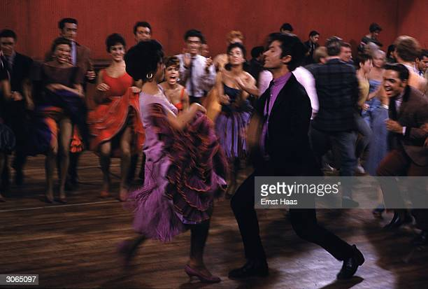 Rita Moreno and George Chakiris attract an audience in a scene from 'West Side Story' directed by Robert Wise and Jerome Robbins